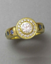 Other Rings 1-9: Round cut diamond surrounded by a bead set frame in 18k yellow gold with flush set blue sapphires down the sides