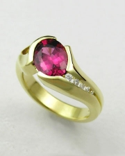 Other Rings 2-4: Oval rhodolite garnet in a partial bezel with channel set diamonds in yellow gold