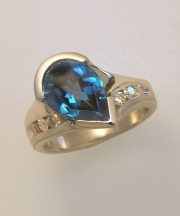 Other Rings 2-8: Pear shaped blue topaz off set in a partial bezel with diamonds in white gold