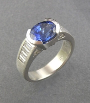 Other Rings 3-2: Oval blue sapphire partial bezel set with diamond baguettes on the sides in platinum