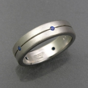 Bands 1-11: Small round blue sapphires set around a grooved line in white gold
