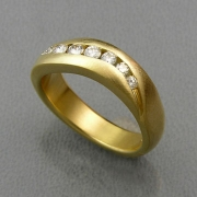Bands 2-12: Curved band with small full cut diamonds channel set in yellow gold