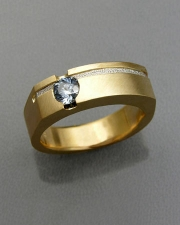 Bands 3-3: Round cut blue sapphire bezel set in yellow gold with a recessed textured platinum inlay