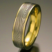 Damascus stainless steel Infinity pattern set in 18kt. Yellow Gold narrow rails, flat band style