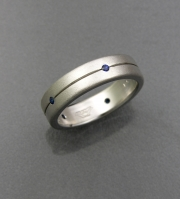 14k White gold Textured band with recessed line, flush set with small Round Blue Sapphires
