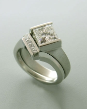 1-1: Princess cut diamond engagement ring set in partial bezel with a twist
