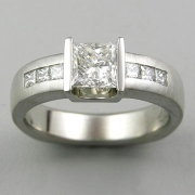 1-11: Princess cut diamond partial bezel set and flanked by channel set smaller princess cut stones on the shank