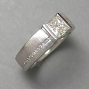 Engagement Ring 1-2: Princess cut diamond channel set in white gold with small channel set side diamonds