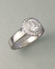 Engagement Ring 1-3: Round cut diamond full bezel set in platinum surrounded by small bead set diamonds