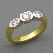 Engagement Ring 1-4: Three round cut diamonds in partial bezel setting in platinum and 18k yellow gold