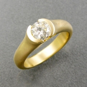 Engagement Ring 1-6: Round cut diamond in an 18k yellow gold partial bezel setting