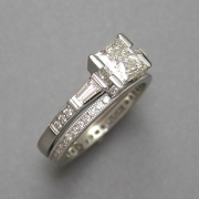 Engagement Ring 1-8: Princess cut diamond in a platinum prong setting with tapered baguettes