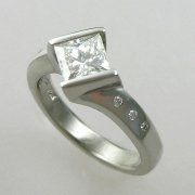 Engagement Ring 2-3: Princess cut diamond channel set in white gold with flush set diamonds down the sides