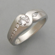 Engagement Ring 2-7: Round cut diamond partial bezel set in white gold with small diamonds channel set down the sides