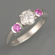 Engagement Ring 2-8: Round cut diamond prong set in white gold with partial bezel set pink sapphires