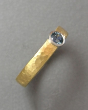 Engagement Ring 3-10: Round cut blue sapphire full bezel set in platinum and 18k yellow gold with a hammered texture
