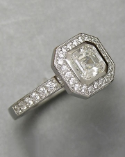Engagement Ring 3-12: Modified emerald cut diamond full bezel set in platinum with bead set diamonds and mill grain detail
