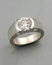 Engagement Ring 3-8: Round cut diamond partial bezel set in platinum with triangular diamonds on the sides