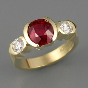 Engagement Ring 4-2: Round cut ruby partial bezel set in yellow gold with partial bezel set side diamonds
