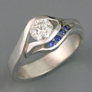 Engagement Ring 4-4: Round cut diamond partial bezel set in platinum with channel set blue sapphires