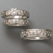 Engagement Ring 4-5: Round cut diamond prong set in white gold with vine details on the sides shown with matching bands