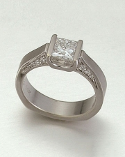 Engagement Ring 4-7: Princess cut diamond channel set in white gold with bead set diamonds in the sides