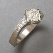 Engagement Ring 4-8: Radiant cut diamond channel set in white gold set at an angle with bead set diamonds on the sides