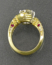 Engagement Ring 5-12: Round cut diamond prong set in 18karat yellow gold with bead set rubies on the sides