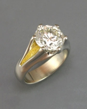 Engagement Ring 5-3: Round cut diamond prong set in platinum with 24karat yellow gold on the sides