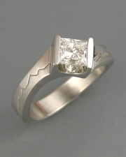 Engagement Ring 5-8: Princess cut diamond channel set in white gold with mountains on the sides