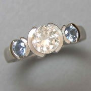 Engagement Ring 5-9: Round cut diamond partial bezel set in white gold with blue Montana sapphires on the sides