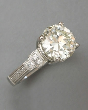 Engagement Ring 7-12: Round cut diamond prong set in platinum with diamonds and mill grain on the sides