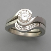 Engagement Ring 7-4: Round cut diamond partial bezel set in white gold shown with matching channel set diamond band