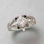 Engagement Ring 8-10: 14kt. white gold engagement ring with princess cut diamond in center surrounded by black diamonds