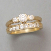 Engagement Ring 9-10: 14kt. yellow gold three stone diamond engagement ring with three partially bezel set round diamonds and a matching diamond channel set wedding band