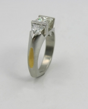 Platinum partial bezel princess cut diamond engagement ring with trillion side stones & 24k inlay