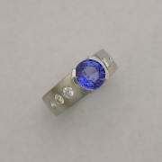 Platinum ring with Sapphire in partial bezel, Flush set side Diamonds